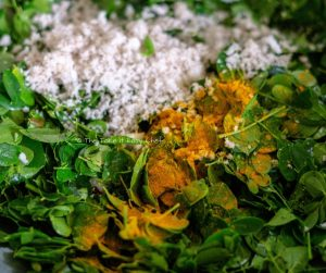 Moringa Leaves Stir-Fry Steps Image - Mixing with grated coconut and turmeric powder