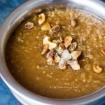 Pradhaman served with a garnish of fried coconut chips, cashews, raisins, and cardamom