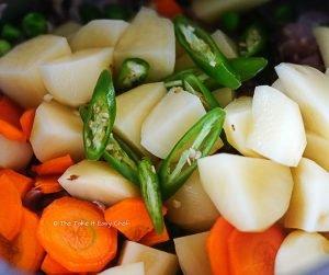 Add mutton, potatoes, carrot, green peas, green chillies, pepper, and salt
