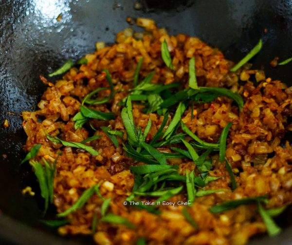Curry leaves (sliced) added to the onion and chilli flake mix
